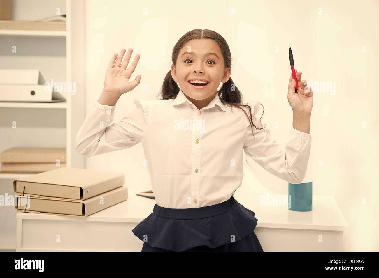 She knows right answer. Child girl wears school uniform standing excited face expression. Schoolgirl smart child looks excited white interior background. Girl remember right answer. Ready to answer. - Stock Image