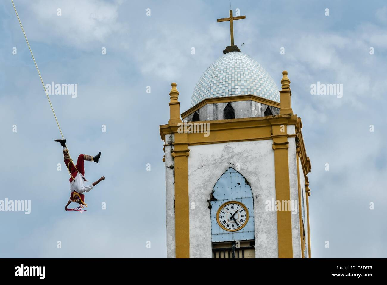 A Volador performs in front of the Church of the Assumption in Papantla, Veracruz, Mexico. The Danza de los Voladores is a indigenous Totonac ceremony involving five participants who climb a thirty-meter pole. Four of these tie ropes around their waists and wind the other end around the top of the pole in order to descend to the ground. The fifth participant stays at the top of the pole, playing a flute and a small drum. The ceremony has been inscribed as a Masterpiece of the Oral and Intangible Heritage of Humanity by UNESCO. - Stock Image