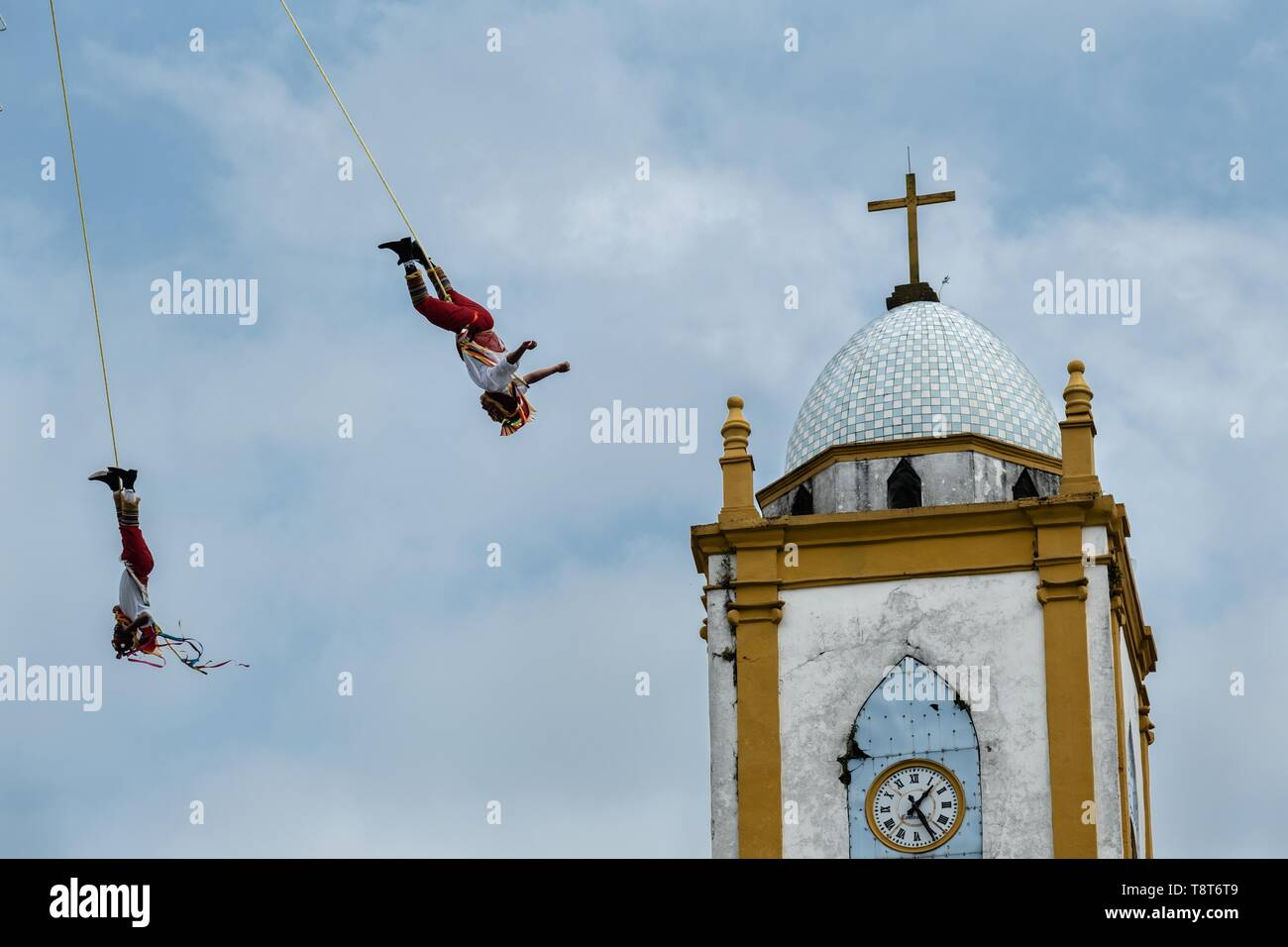 Voladores performs in front of the Church of the Assumption in Papantla, Veracruz, Mexico. The Danza de los Voladores is a indigenous Totonac ceremony involving five participants who climb a thirty-meter pole. Four of these tie ropes around their waists and wind the other end around the top of the pole in order to descend to the ground. The fifth participant stays at the top of the pole, playing a flute and a small drum. The ceremony has been inscribed as a Masterpiece of the Oral and Intangible Heritage of Humanity by UNESCO. - Stock Image