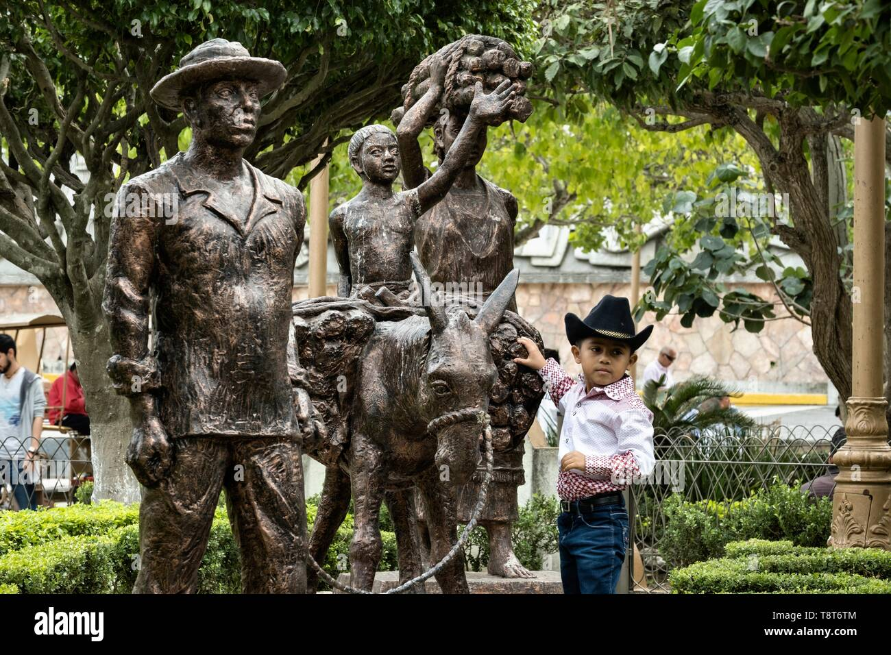 A young Mexican boy poses by a statue honoring the indigenous Totonac people in the Plaza Central Israel Tellez Park in Papantla, Veracruz, Mexico. - Stock Image
