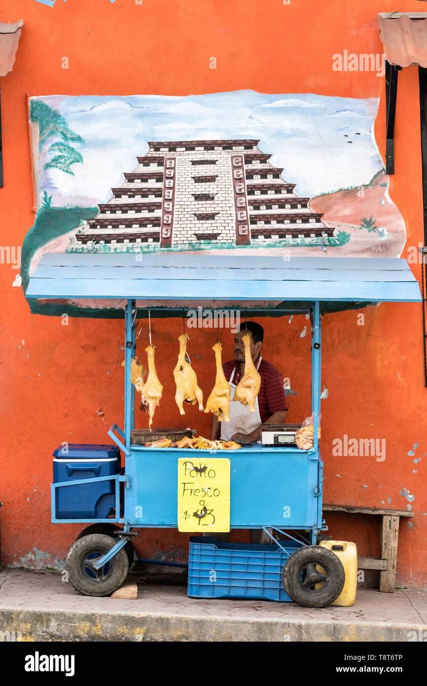 A Mexican food vendor sells fresh chickens under a mural of the El Tajin pyramid outside the central Market in Papantla, Veracruz, Mexico. Stock Photo