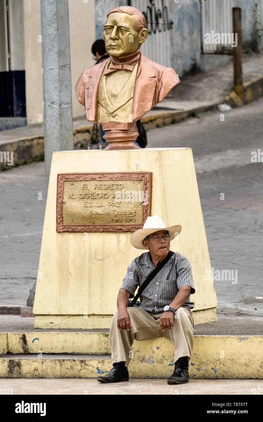 A Mexican sits under a bust of Benito Juarez in Papantla, Veracruz, Mexico. - Stock Image