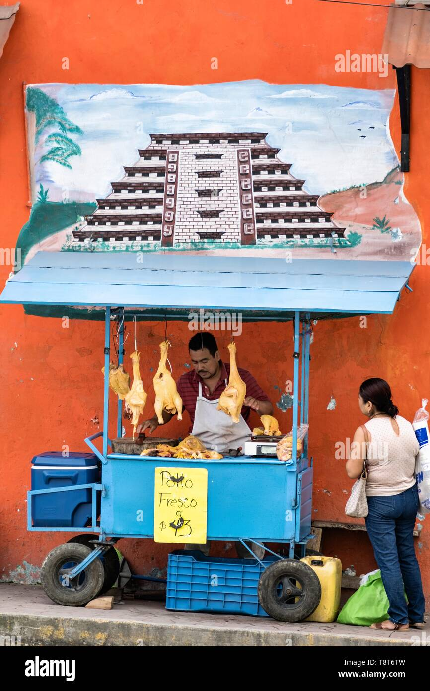 A Mexican food vendor sells fresh chickens under a mural of the El Tajin pyramid outside the central Market in Papantla, Veracruz, Mexico. - Stock Image