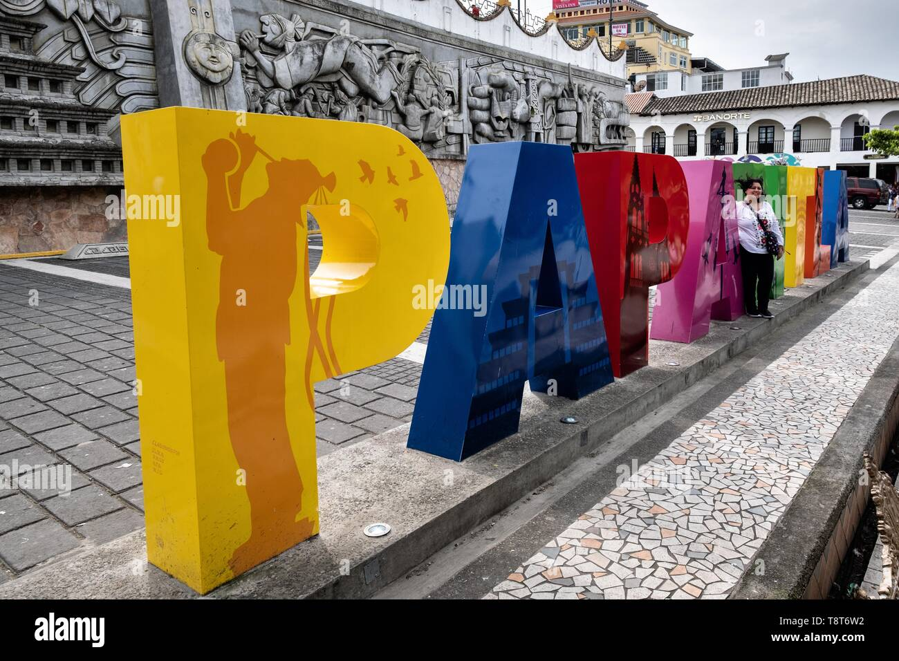 A poses at the city sign in front of the sculpture; Evolution of the Totonac culture by Teodoro Cano Garcia, in the Plaza Central Israel Tellez Park in Papantla, Veracruz, Mexico. - Stock Image