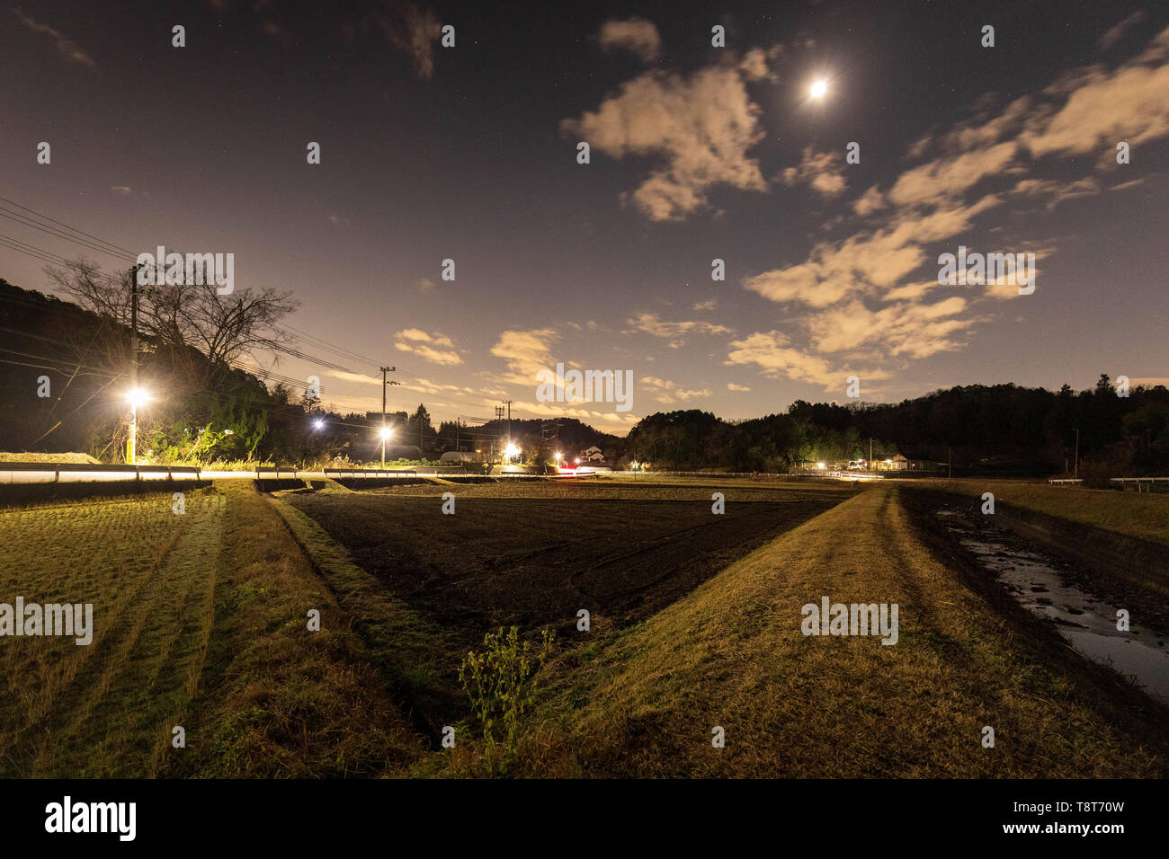 Bright moon shines in night sky over rural rice fields in Kyoto Prefecture - Stock Image