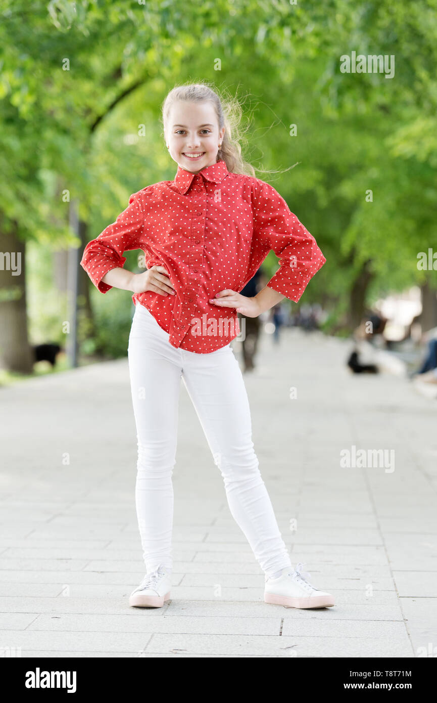 Charming stylish fashionable girl in park. Little child enjoy walk in park. Weekend walk. Girl carefree child. Kid walking sunny day. Summer holidays. Emotional kid in park nature background. - Stock Image