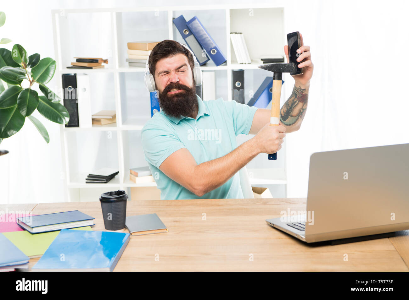 Stressful job at call center. Man bearded guy headphones office hammer smartphone. Spoiled communication. Failed mobile negotiations. Most annoying thing about work in call center. Incoming call. - Stock Image