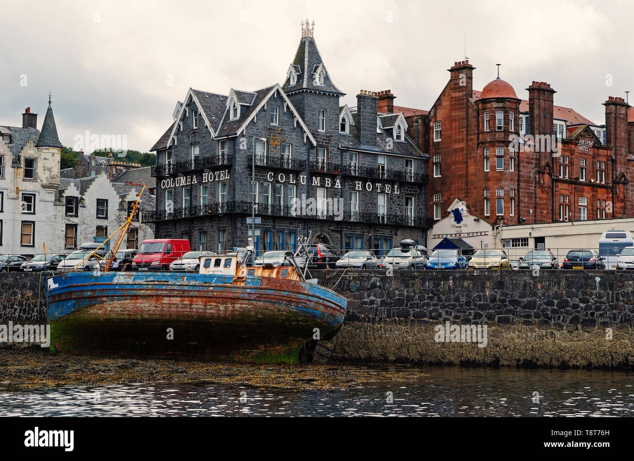 Oban, United Kingdom - February 20, 2010: shipwreck and city architecture along sea quay. Bay with houses on grey sky. Resort town with hotels. Summer vacation on island. Travelling and wanderlust. - Stock Image