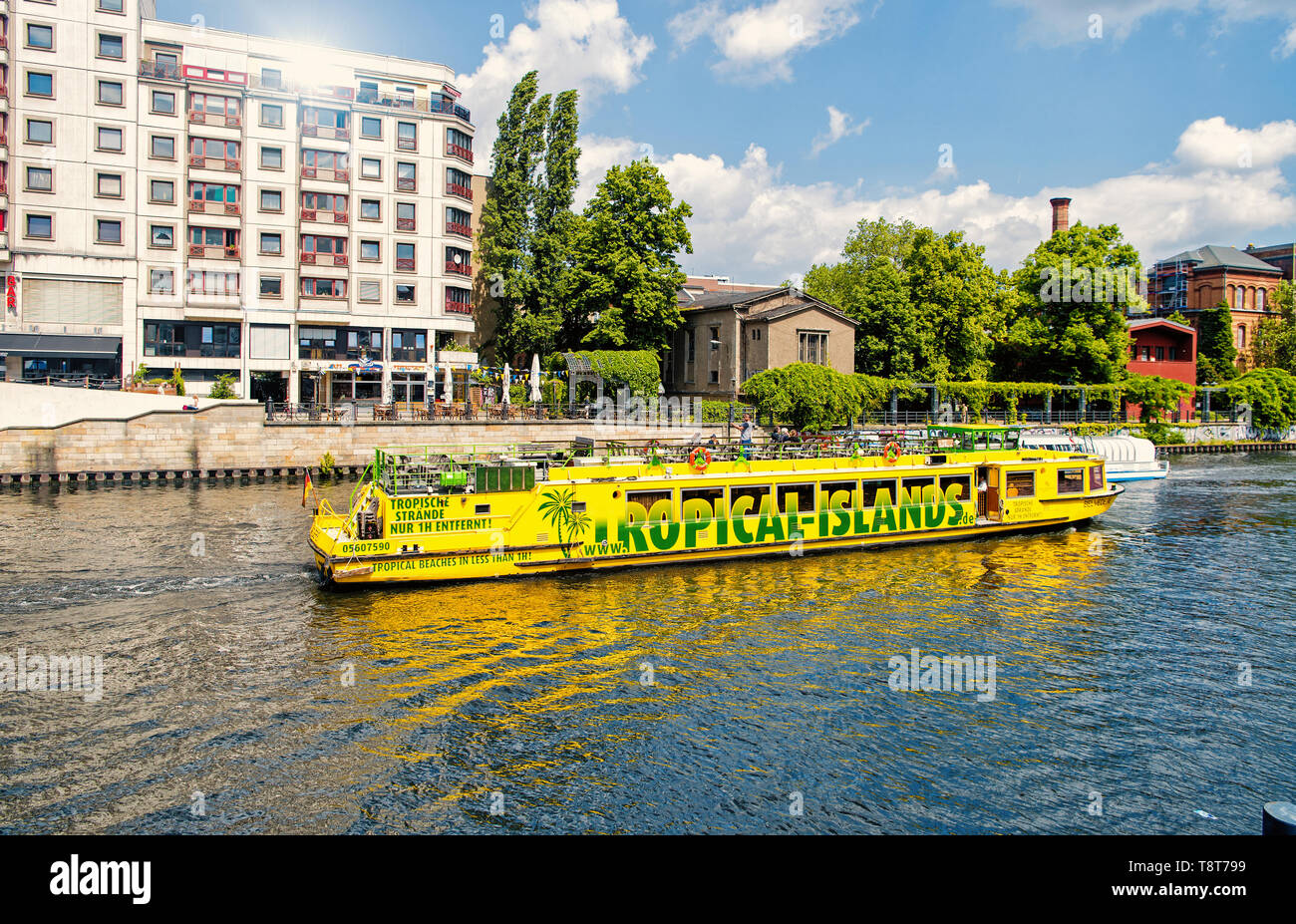Berlin, Germany - May 31, 2017: tour by river on yellow boat with tourists along city canal on skyline background. Travelling and trip, concept - Stock Image