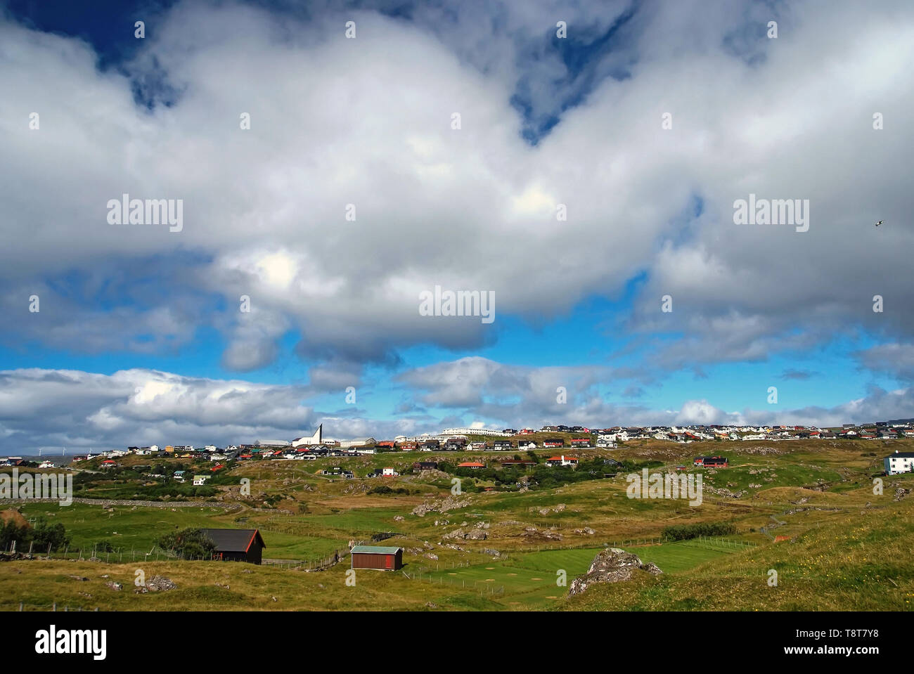 Country landscape with farmhouses under cloudy sky in Torshavn, Denmark. Beautiful landscape view. Hilly terrain with green grass. Overcast sky. Nature and environment. Summer vacation in countryside. - Stock Image