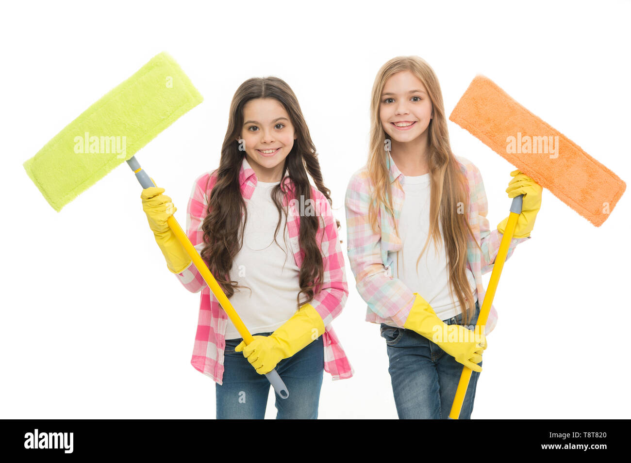 Sisters hold wet mops ready start cleaning day. Girls cute kids cleaning around. Keep it clean. Helpful cheerful kids cleaning together. Girls with protective gloves and mops ready for cleaning. - Stock Image