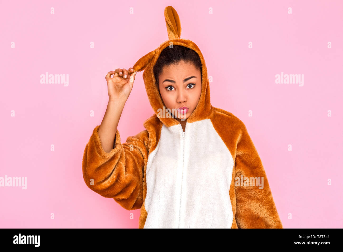 Young woman in bunny kigurumi standing isolated on pink background touching rabbit ear pouting lips grimacing to camera - Stock Image