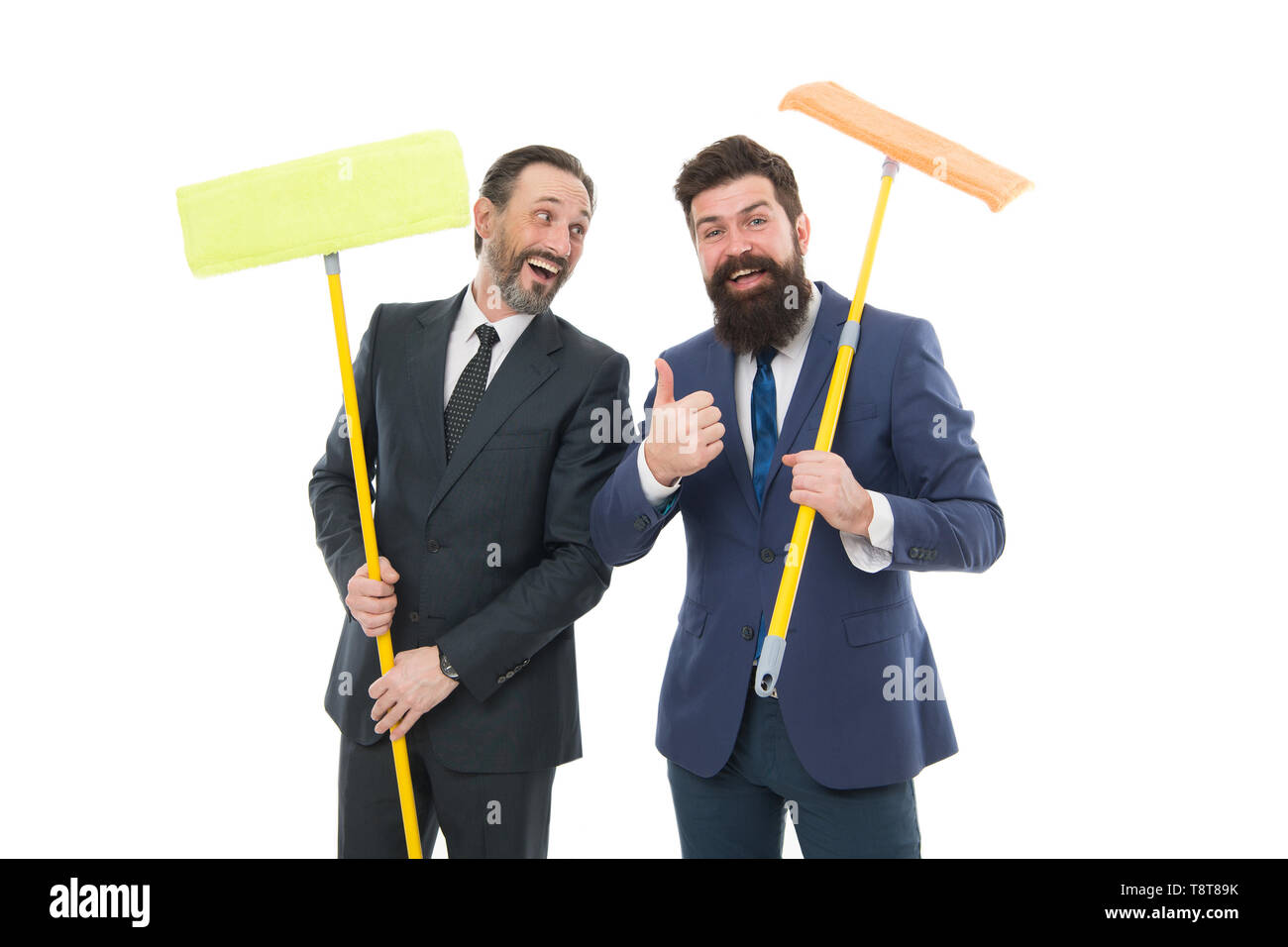 Big cleaning day. Cleaning business. Household duties. Cleaning service concept. Cover our tracks before someone find out financial fraud. Clear reputation. Bearded men formal suits hold mops. - Stock Image