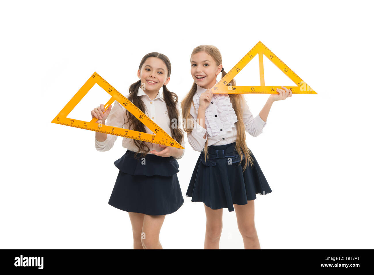 Favorite school subject. Education and school concept. School students learning geometry. Kids school uniform isolated white. STEM concept. Learn theorem about right angle. Girls with big rulers. - Stock Image