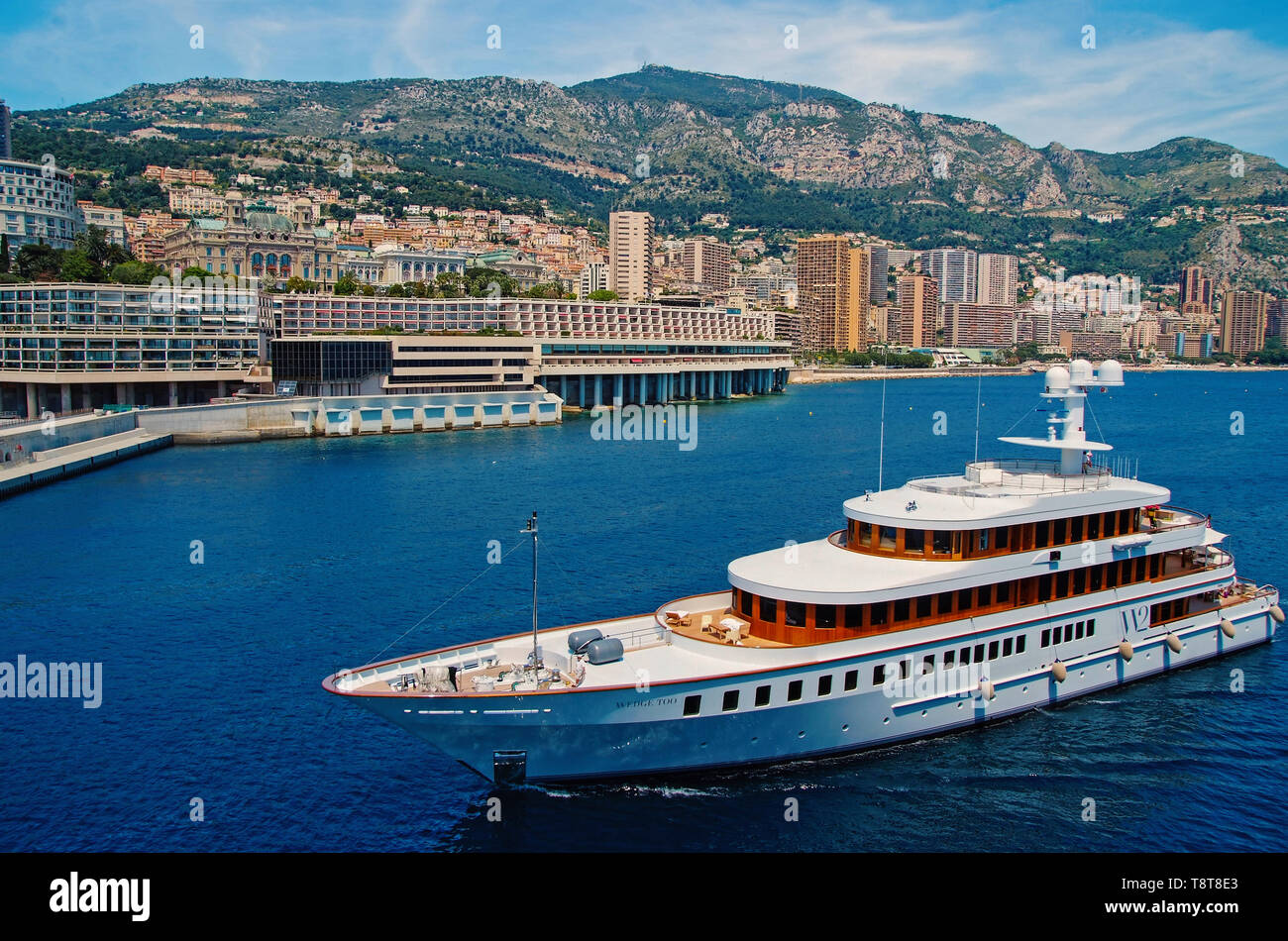 Monte Carlo, Monaco - December 08, 2009: W2 Wedge Too yacht go along sea coast. Water craft and city on mountain landscape. Luxury lifestyle. Pleasure and sport. Summer vacation and wanderlust. - Stock Image