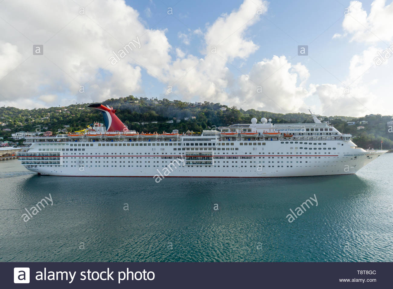 The cruise ship Carnival Fascination begins to depart the harbor at Castries on the island of Saint Lucia, West Indies, Caribbean Sea - Stock Image