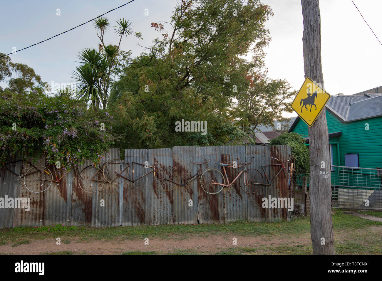 A sign in a country suburban street warning drivers of horse riders ahead and a corrugated iron fence with decorative bicycle parts stuck to it. - Stock Image