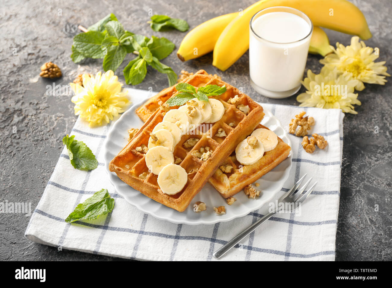 Delicious waffles with banana slices and glass of milk on grey table - Stock Image