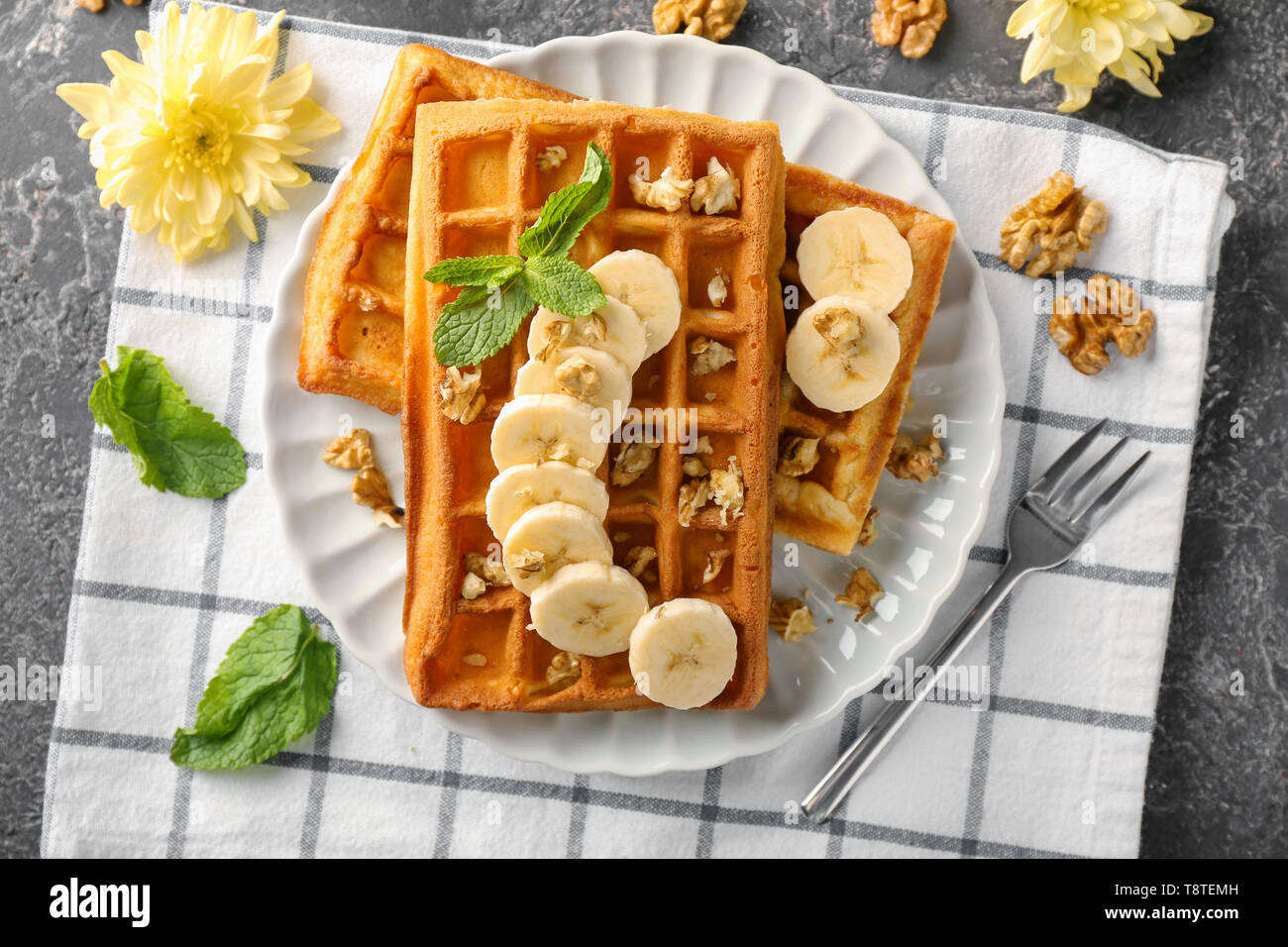 Delicious waffles with banana slices and nuts on plate - Stock Image