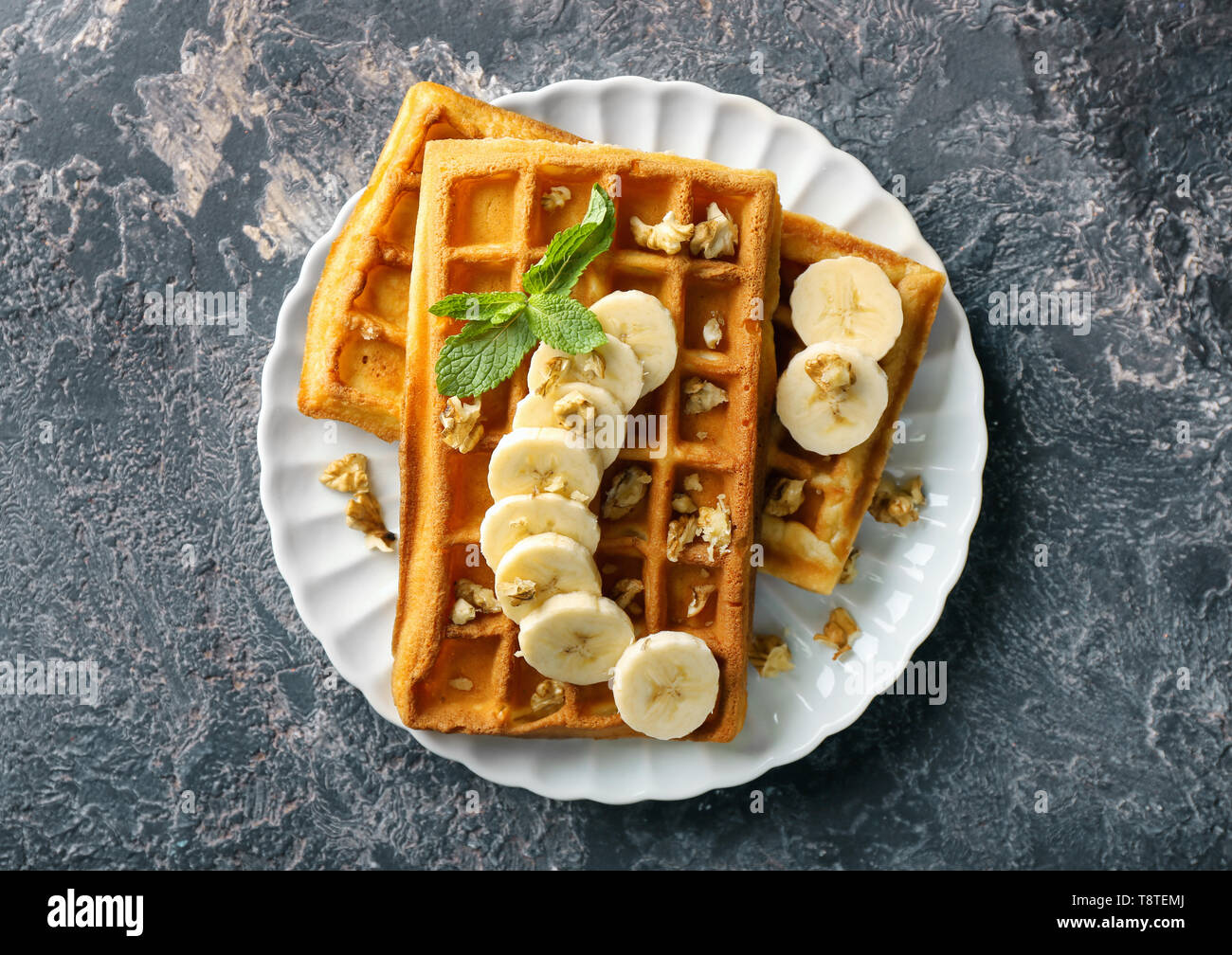 Delicious waffles with banana slices and nuts on grunge background - Stock Image