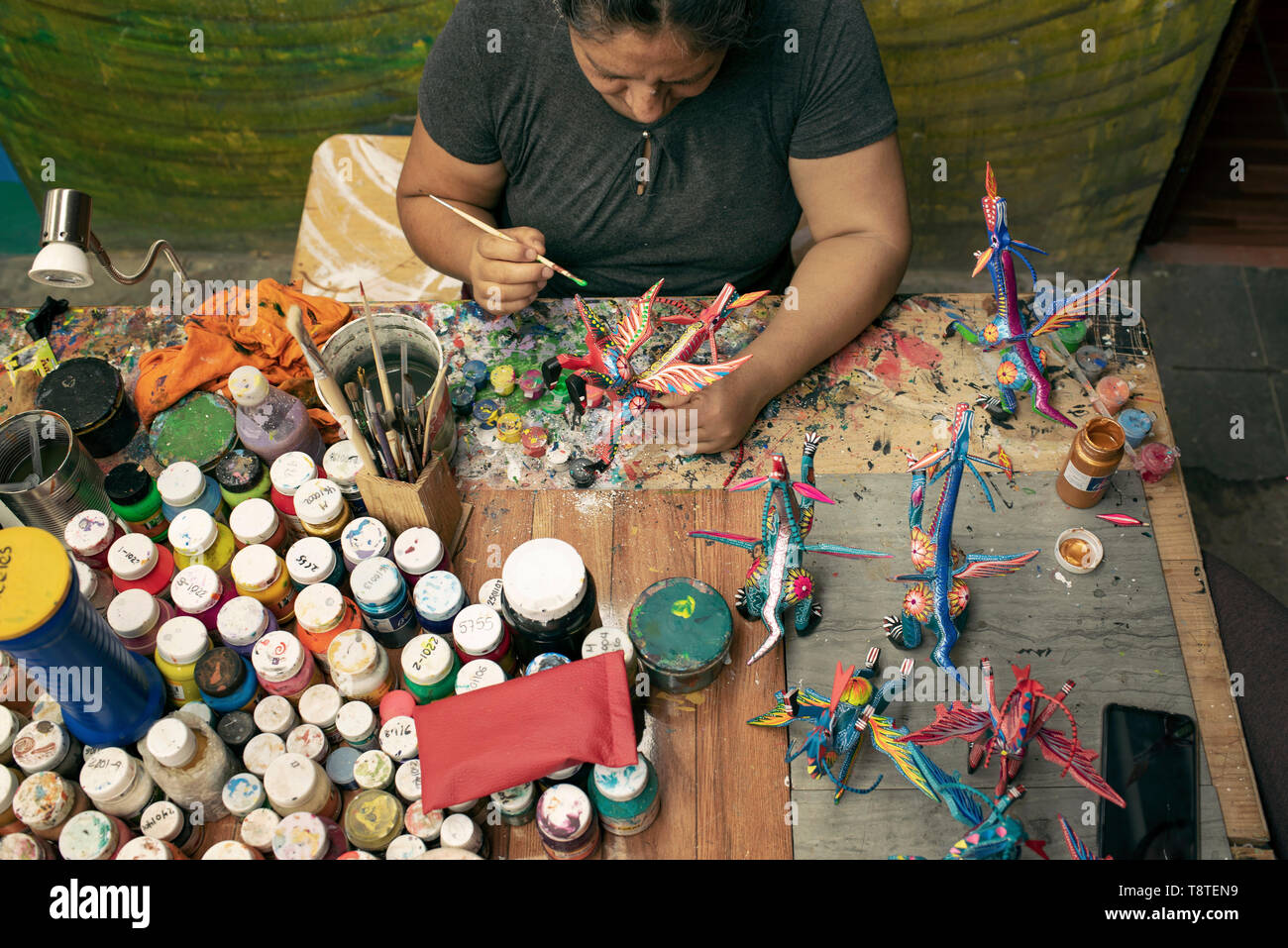 Mexican woman painting alebrijes (surreal dream-like wooden sculptures). San Martín Tilcajete, Oaxaca, Mexico. Apr 2019 - Stock Image