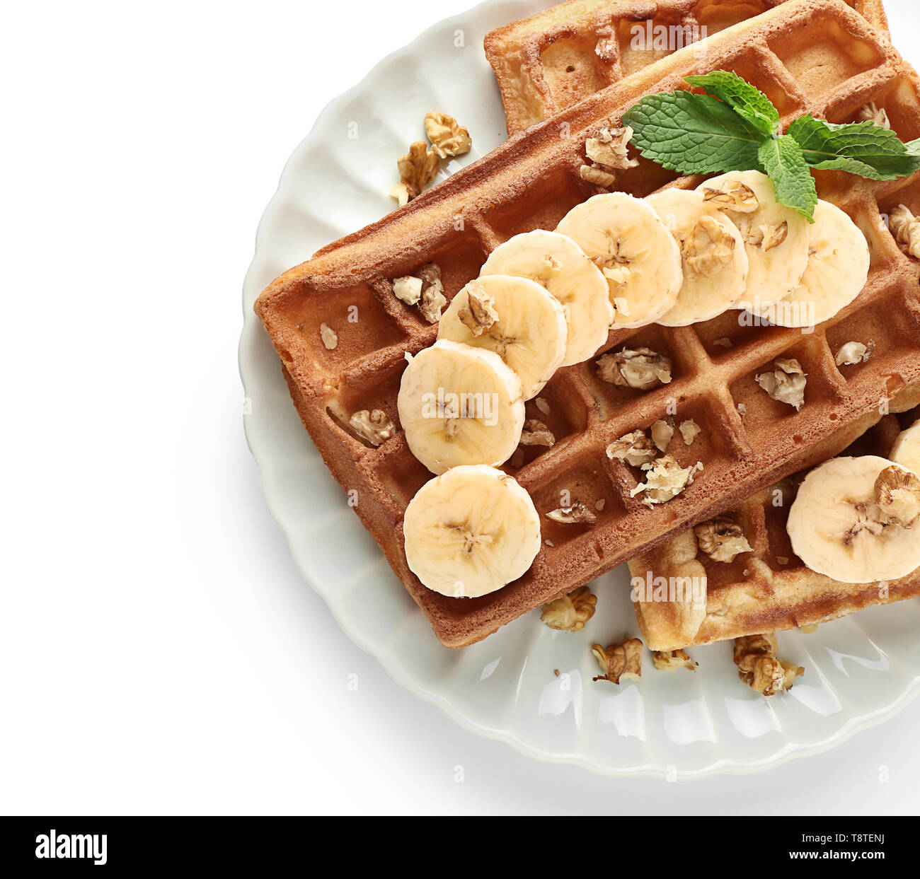 Delicious waffles with banana slices and nuts on white background - Stock Image