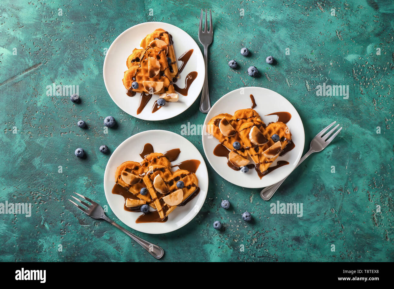 Heart shaped waffles with banana slices and chocolate sauce on color background - Stock Image
