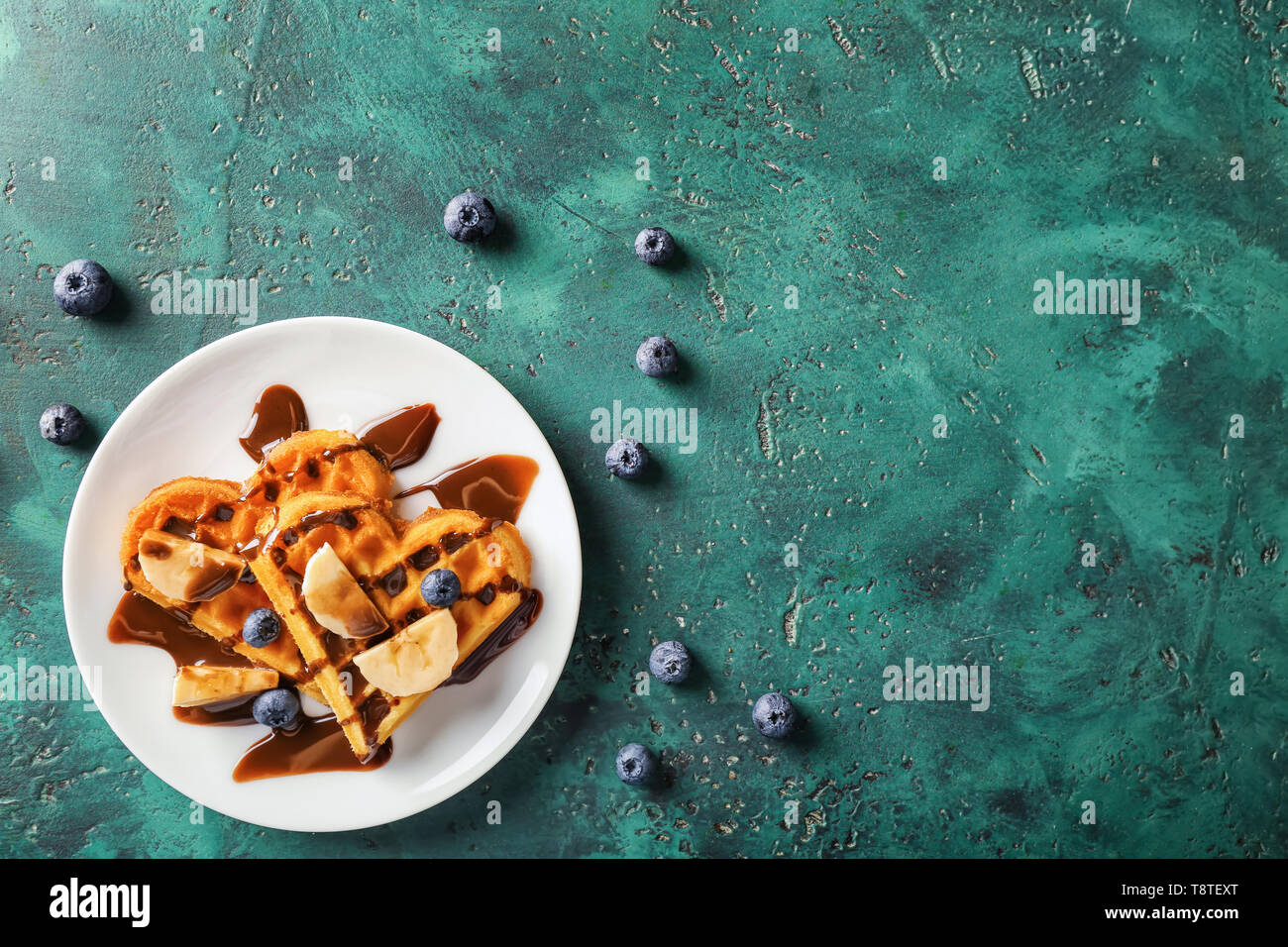 Heart shaped waffles with banana slices, blueberries and chocolate sauce on color table - Stock Image