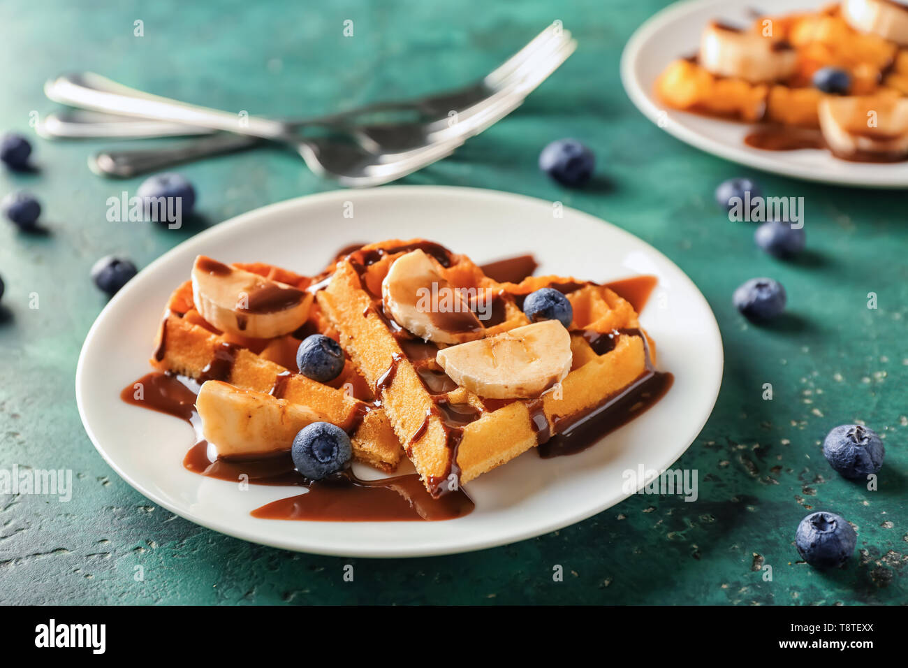 Heart shaped waffles with banana slices, blueberries and chocolate sauce on plate - Stock Image