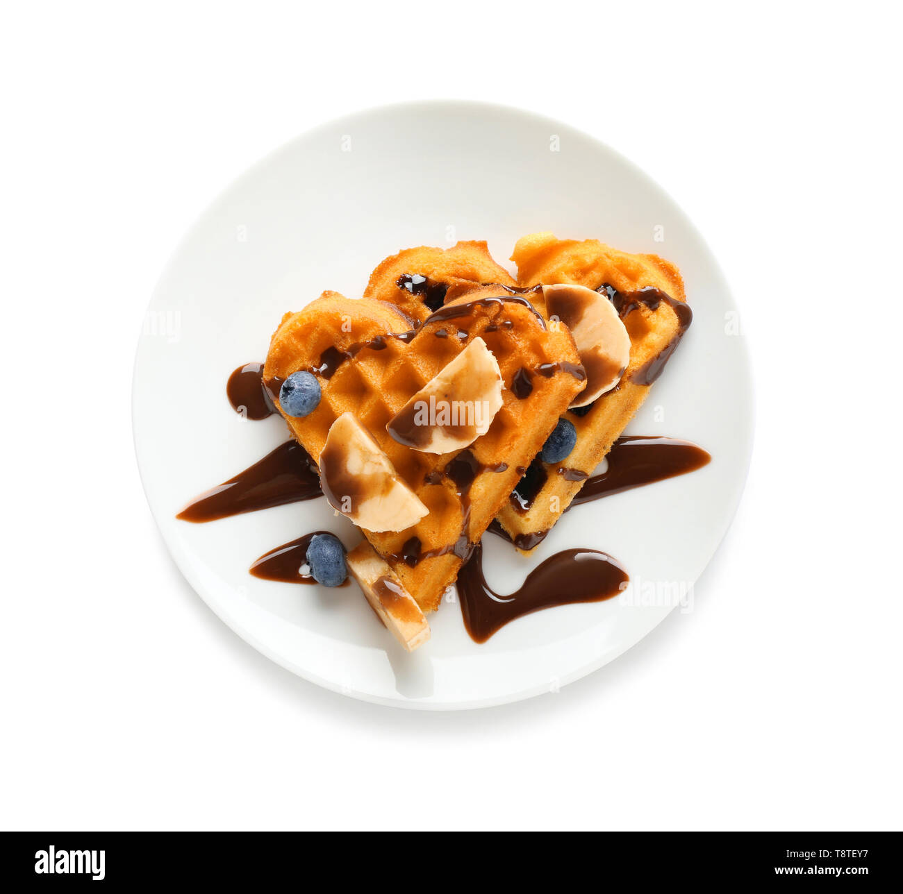 Heart shaped waffles with banana, blueberries and chocolate sauce on white background - Stock Image