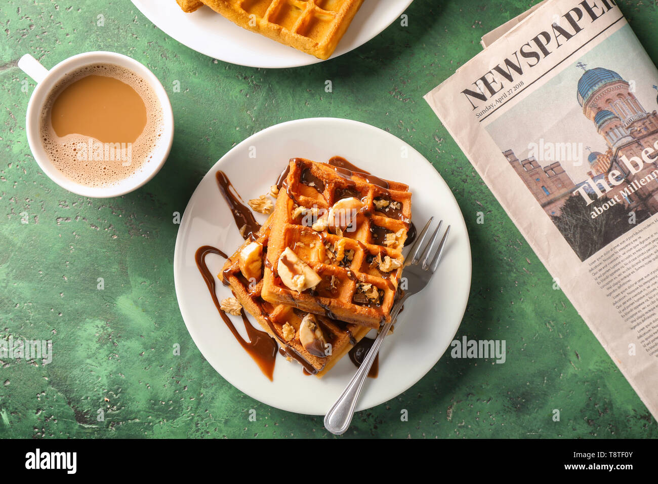 Delicious waffles with cup of coffee and newspaper on color table - Stock Image