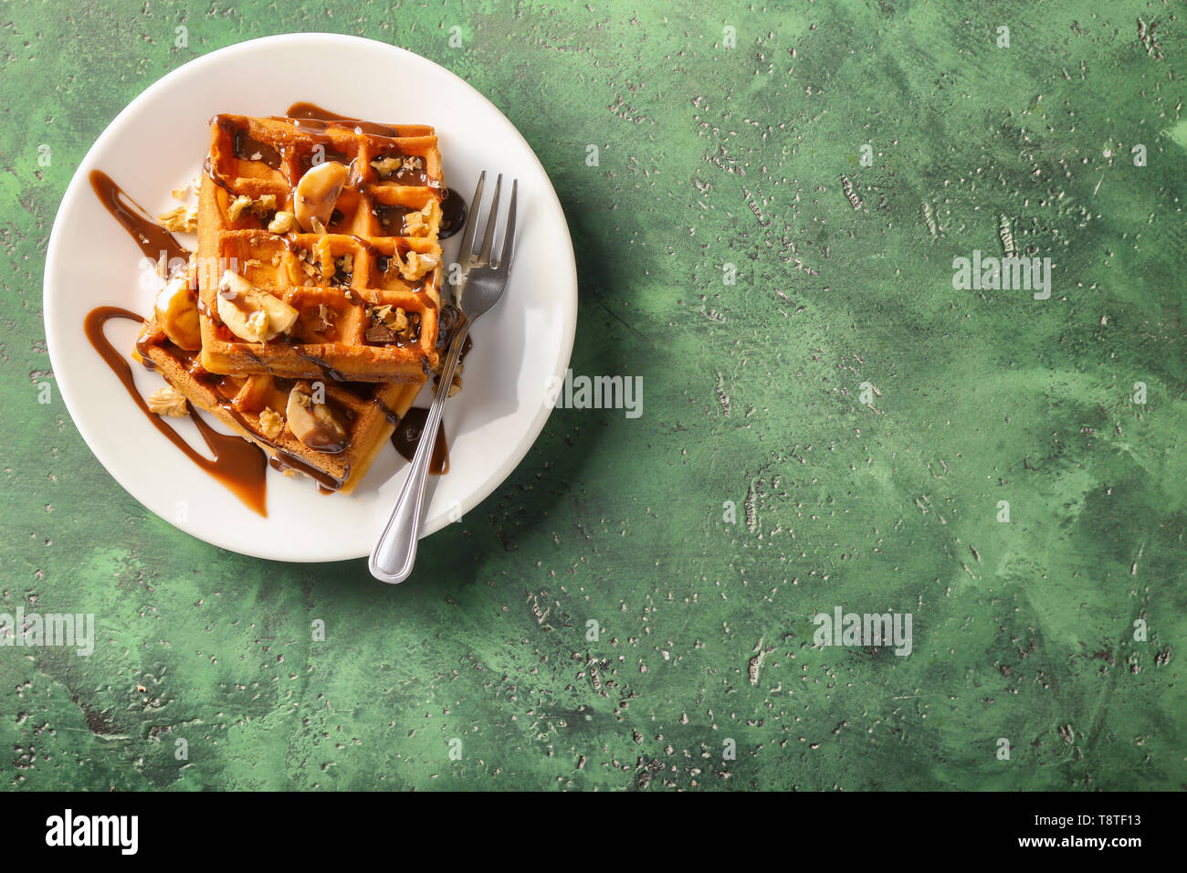 Delicious waffles with banana slices and chocolate sauce on color table - Stock Image
