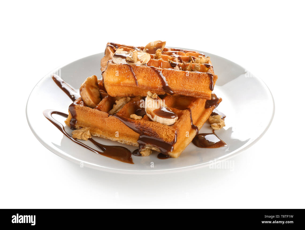 Delicious waffles with banana slices and chocolate sauce on white background - Stock Image