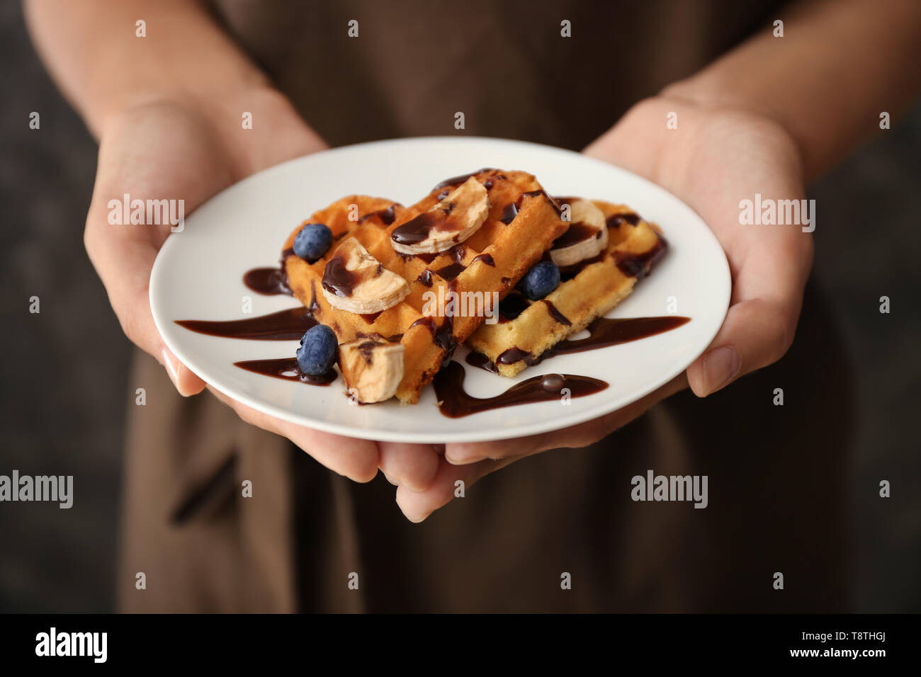 Woman holding plate with tasty waffles and berries, closeup - Stock Image