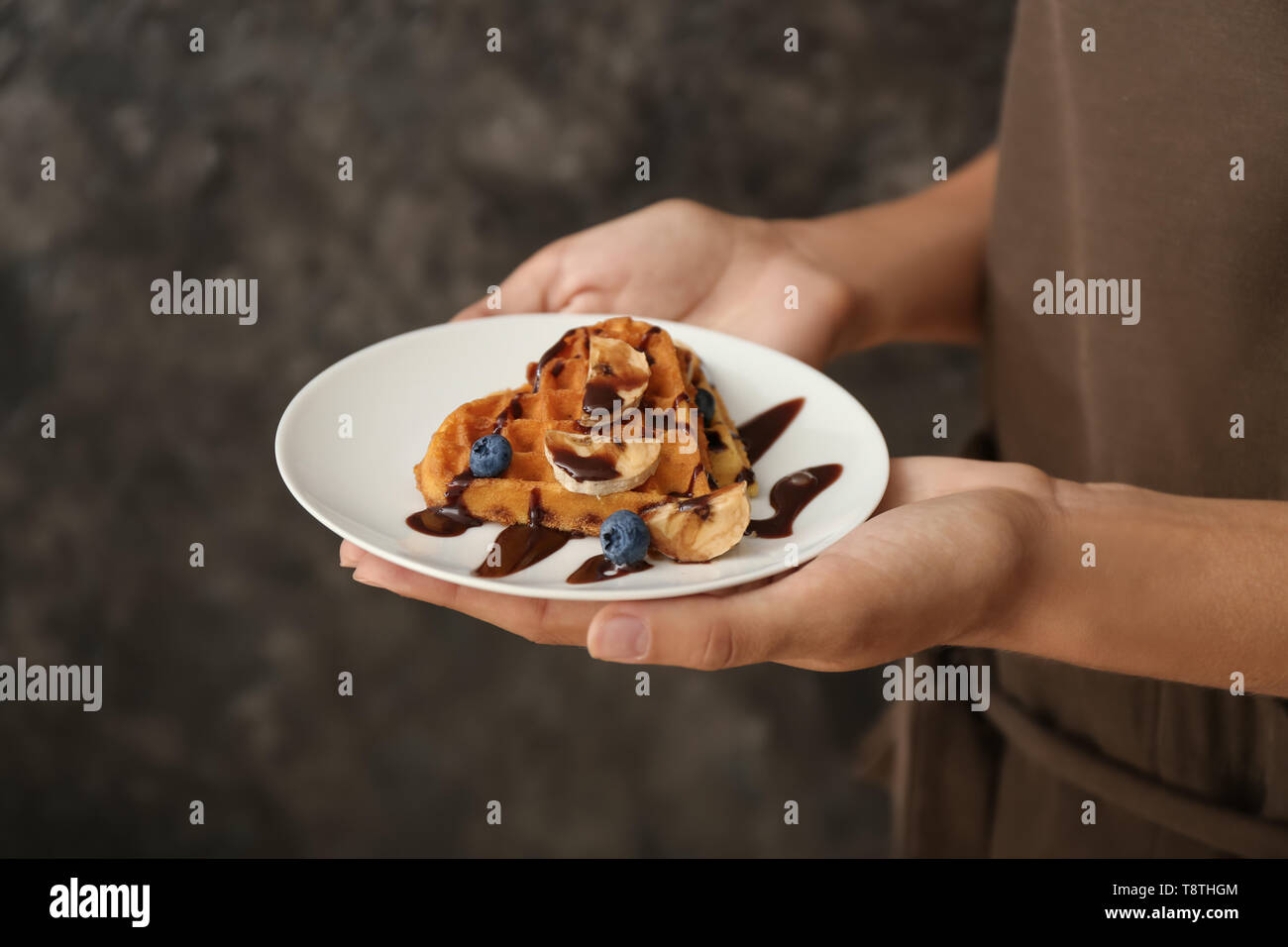 Woman holding plate with tasty waffles and berries on grey background, closeup - Stock Image