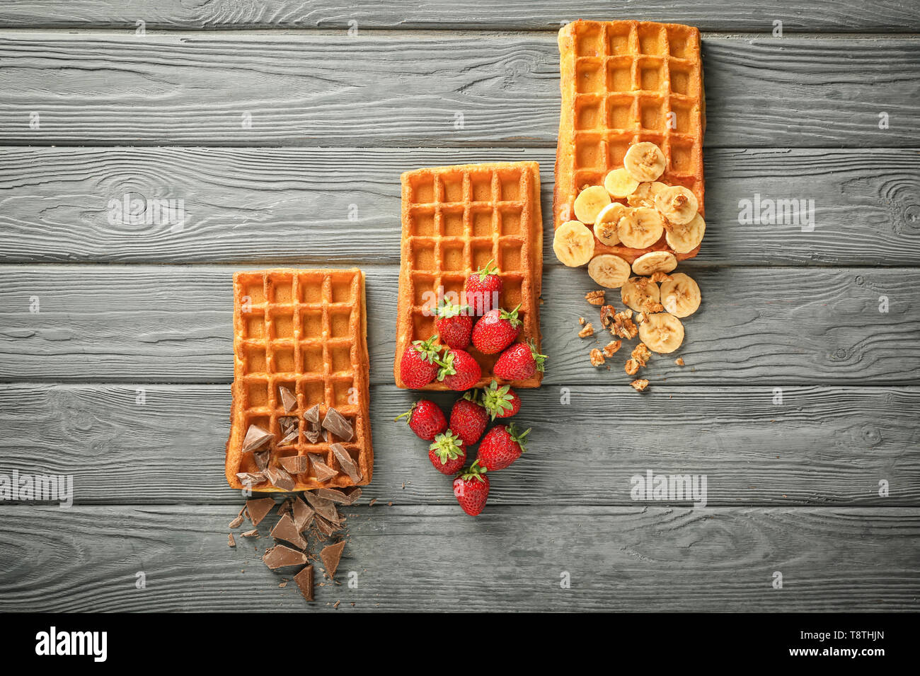 Delicious waffles with banana, berries and chocolate on wooden background, flat lay - Stock Image