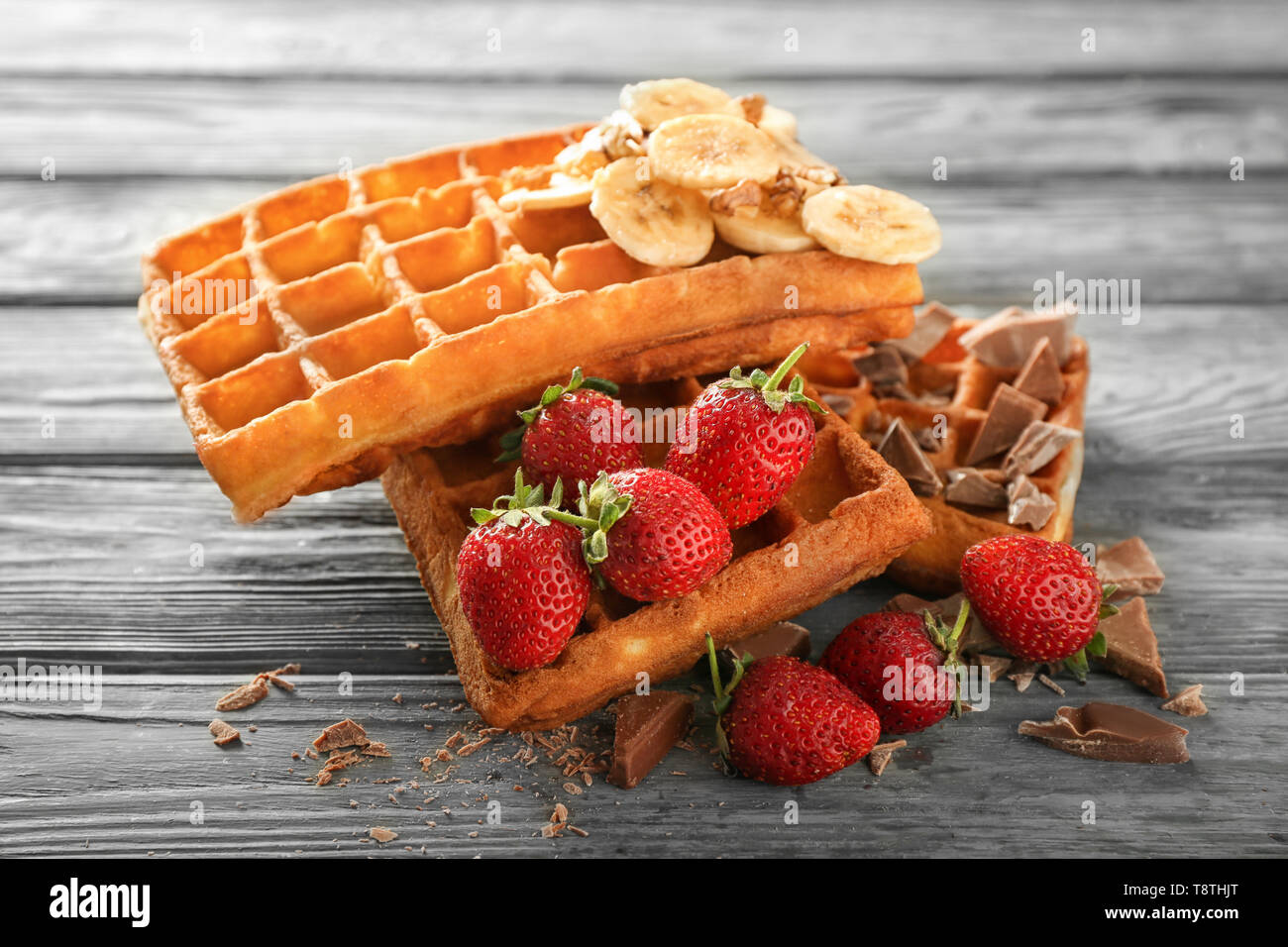 Delicious waffles with banana, berries and chocolate on wooden background - Stock Image