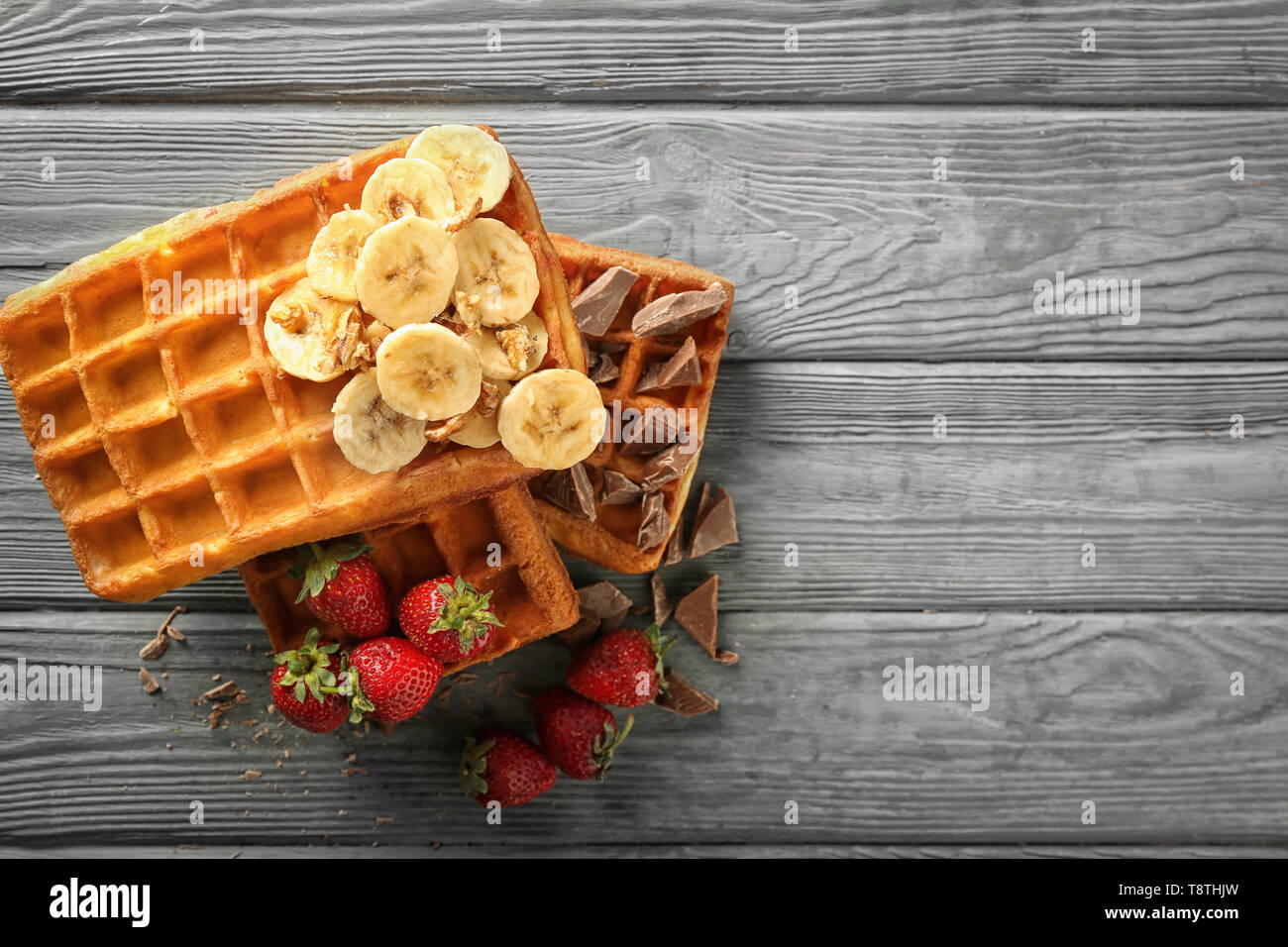 Delicious waffles with banana, berries and chocolate on wooden background, top view - Stock Image