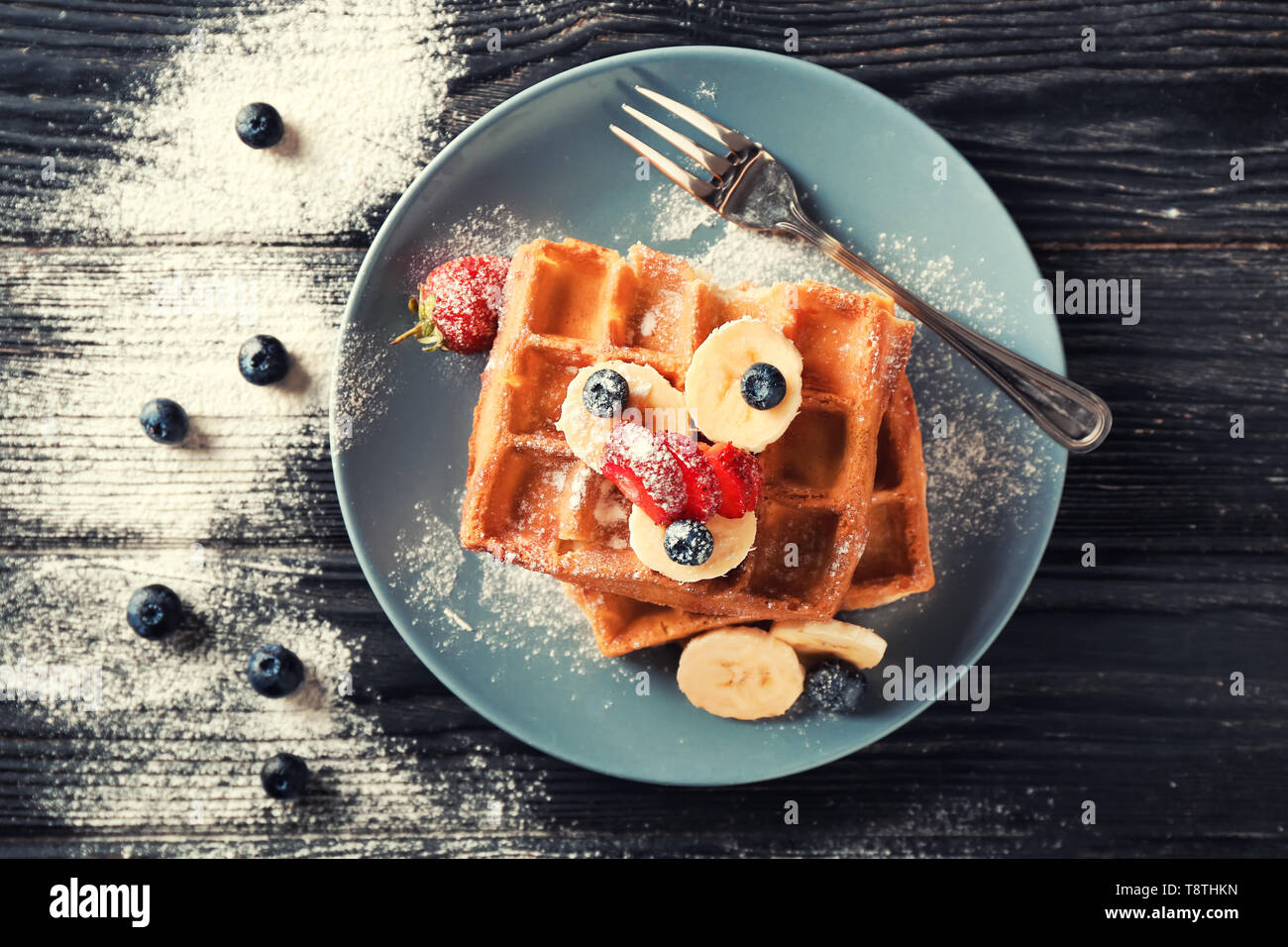 Plate with delicious waffles and berries on wooden table - Stock Image