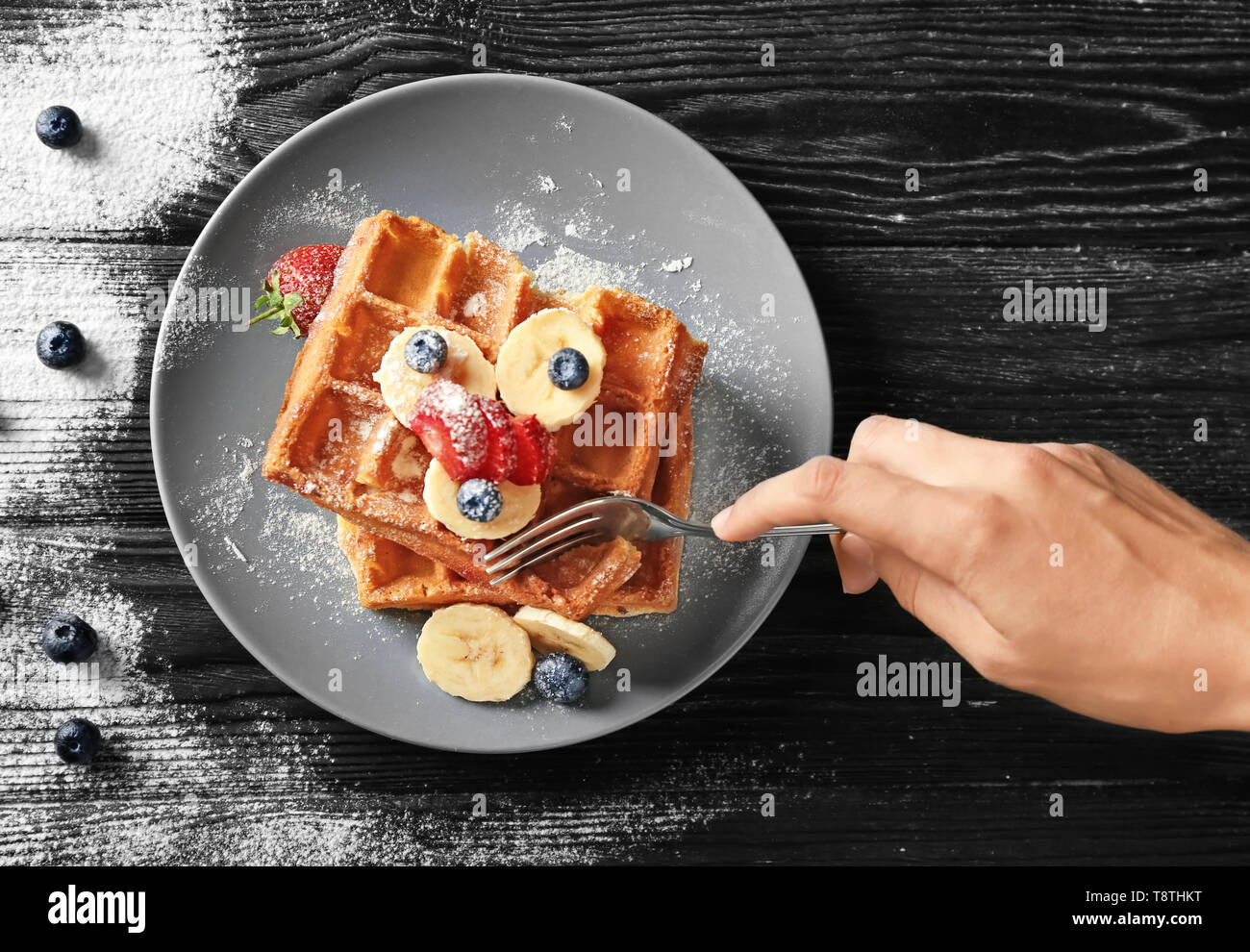 Woman eating delicious waffles and berries on wooden background - Stock Image