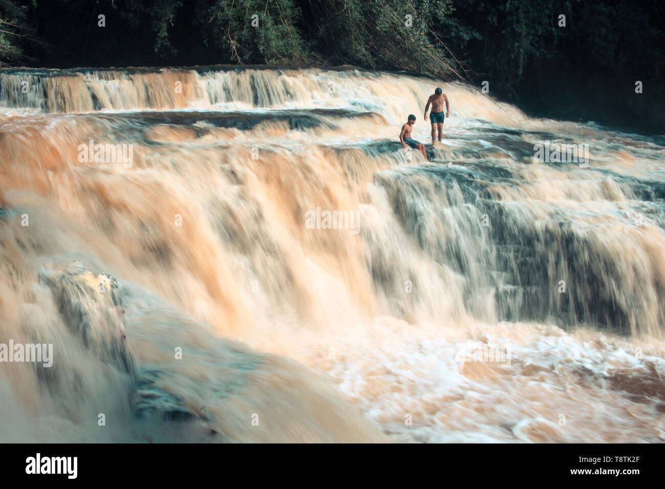 two children playing in a waterfall in nature - Stock Image
