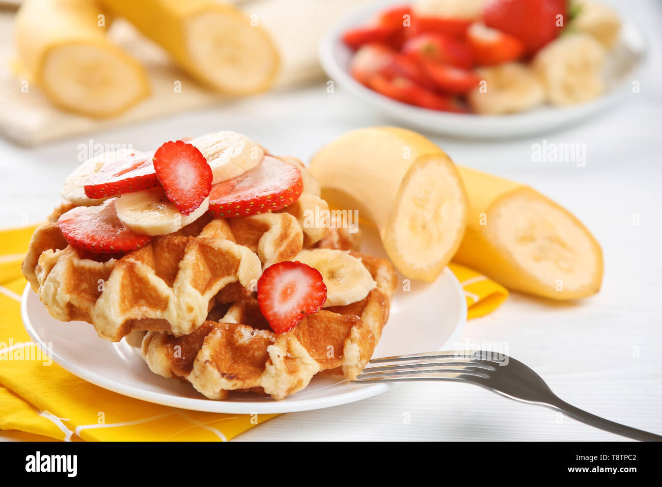 Delicious waffles with strawberry and banana slices on plate - Stock Image