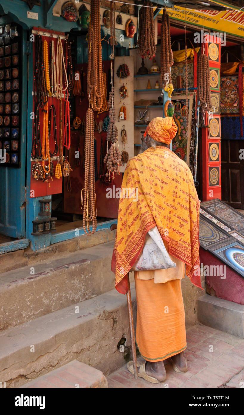 Hindu sadhu (holy man) outside shop selling beads and other handicrafts in market near Durbar Square, Patan, Kathmandu Valley, Nepal - Stock Image