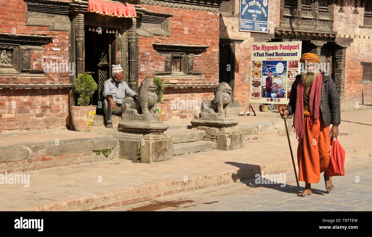 A Hindu sadhu (holy man) walks past old brick buildings on Durbar Square, Patan, Kathmandu Valley, Nepal - Stock Image