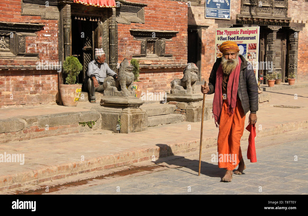 A Hindu sadhu (holy man) walks past old brick buildings on Durbar Square, Patan, Kathmandu Valley, Nepal - Stock Image