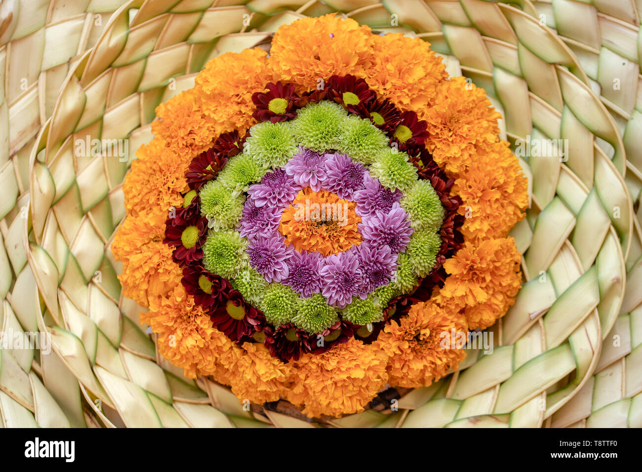 A wreath of straw and flowers for religious ceremonies in Ubud, island Bali, Indonesia , close up - Stock Image