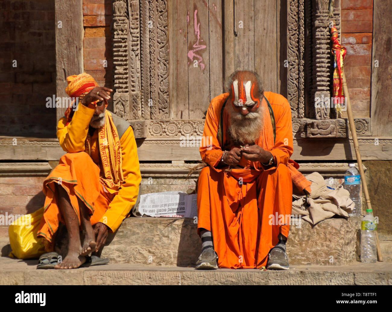 Hindu sadhus (holy men) sitting on the steps of a building in Durbar Square, Kathmandu, Nepal - Stock Image