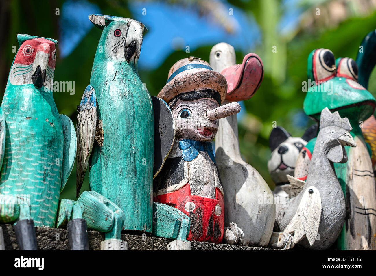 Old wooden souvenirs toys on the stone fence near the doll shop in Ubud, Bali island, Indonesia. Close up - Stock Image