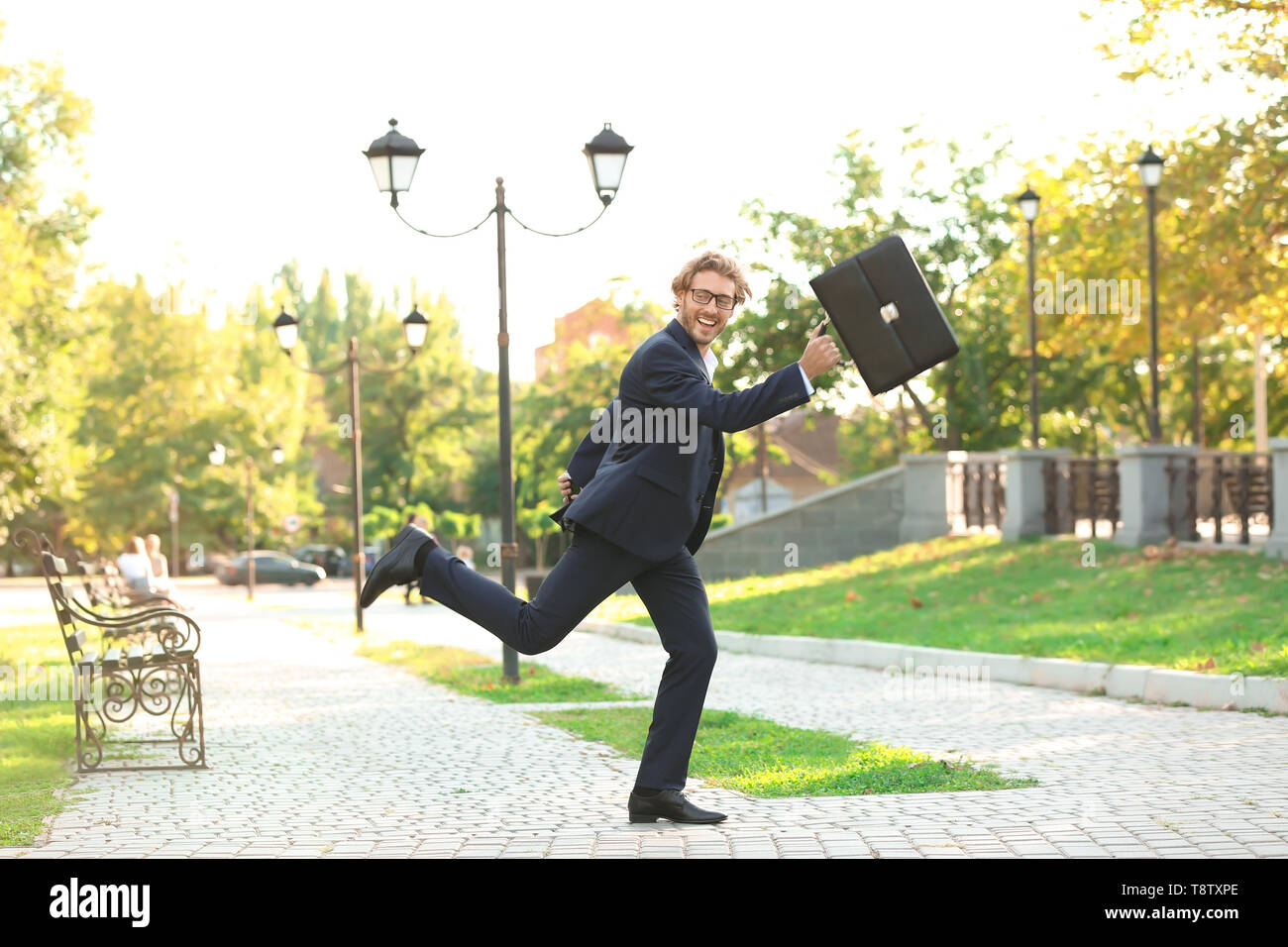 Handsome young man with briefcase running in park - Stock Image