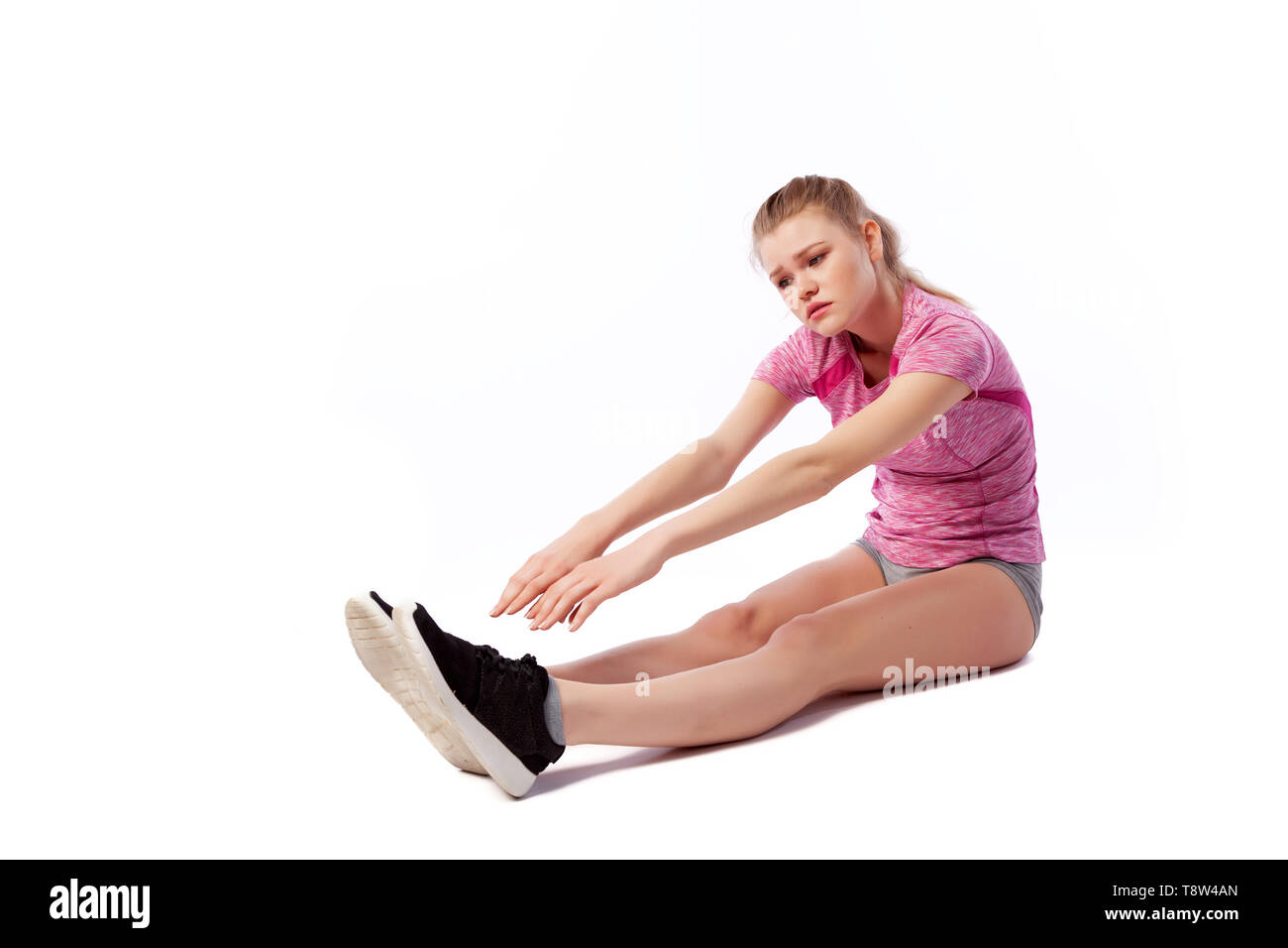 Young woman in sports clothes smilling, possing and stretching on the floor on white isolated background. Side view.Fit girl living an active lifestyl - Stock Image